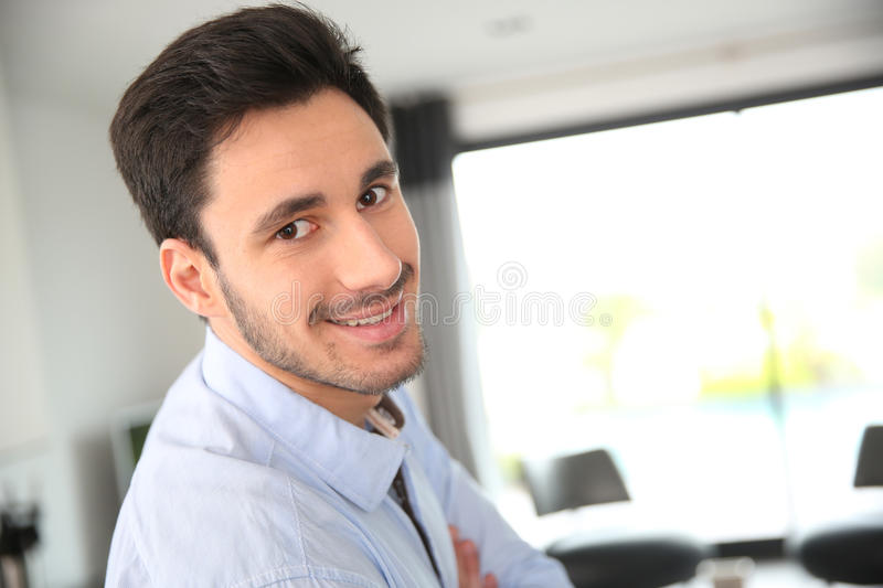 Smiling man standing in living-room. Portrait of smiling man standing in living-room royalty free stock images