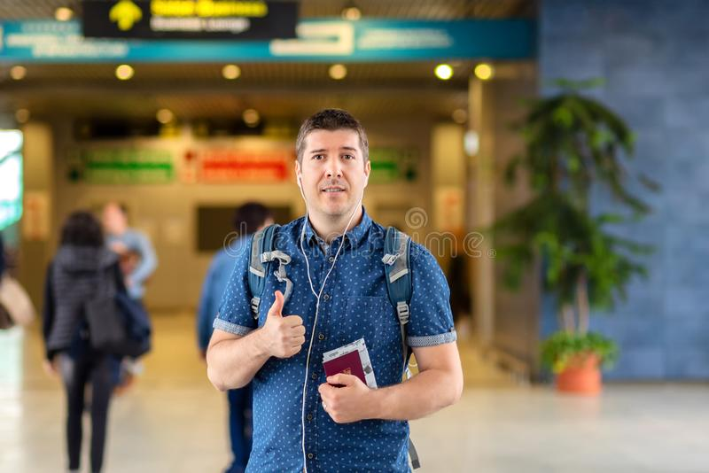 Smiling man standing at modern airport departure terminal holding passport and boarding pass royalty free stock photos