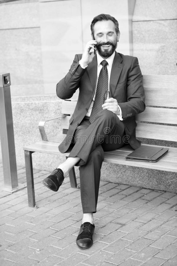 Smiling man in suit sitting on bench and phoning. Handsome smiled young businessman siting on bench with his laptop next to office. While talking on his phone stock images
