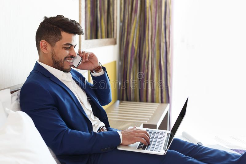 Smiling man in suit talking on phone, working at hotel stock photography