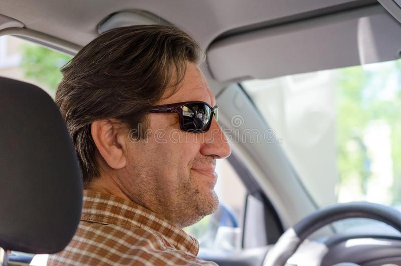 Smiling man in sunglass driving car royalty free stock images