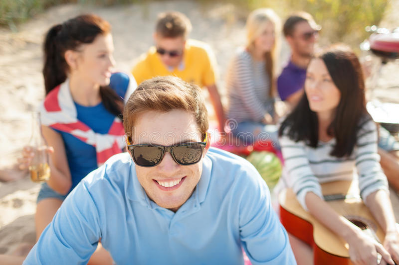 Smiling man in sunglasses on the beach. Summer, holidays, vacation and happiness concept - smiling men in sunglasses having fun on the beach with company on the royalty free stock photos