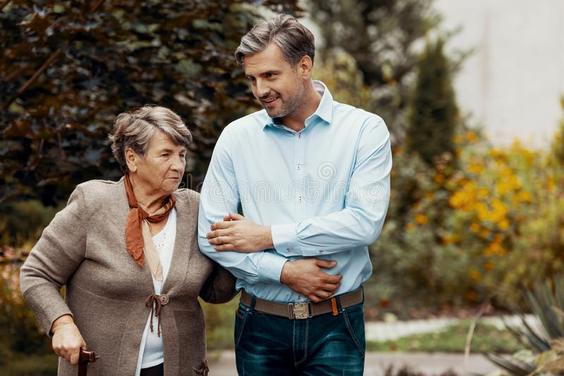 Man supporting senior woman while walking in the garden royalty free stock photo