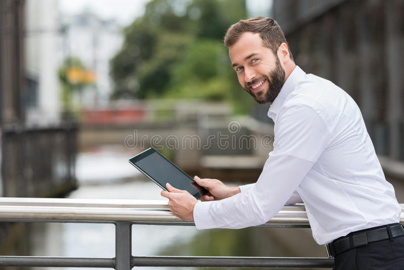 Smiling man surfing the web on his tablet royalty free stock images