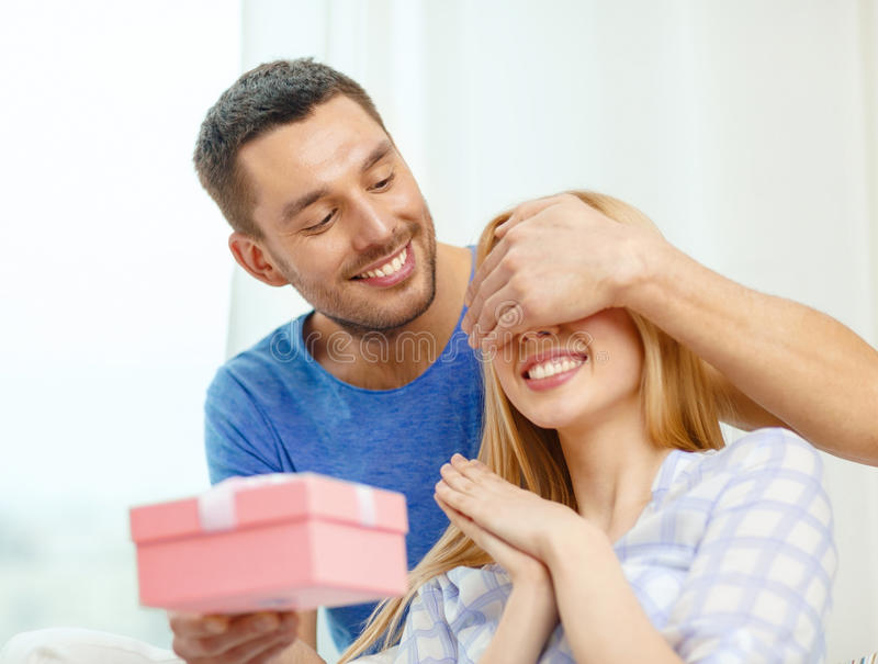 Smiling man surprises his girlfriend with present stock image