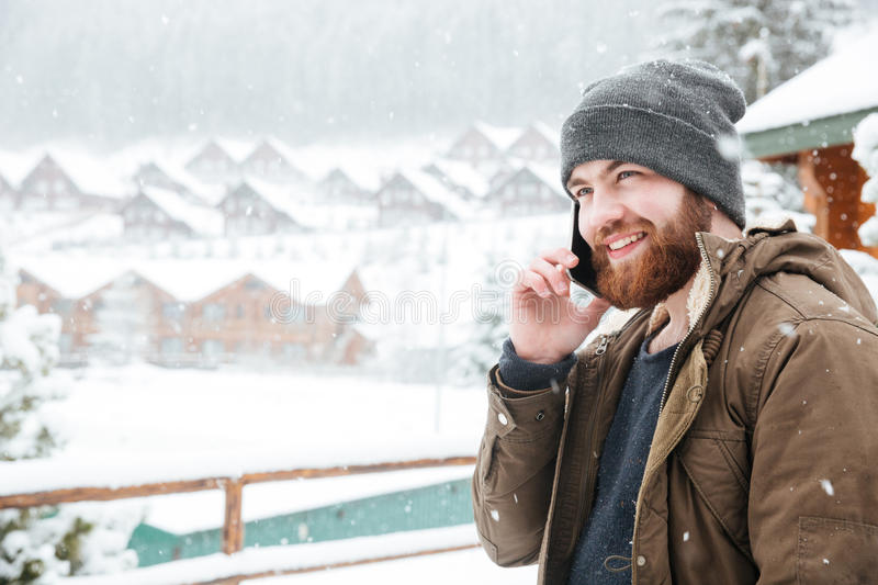 Smiling man talking on cell phone outdoors in snowy weather. Smiling attractive young man with beard talking on cell phone outdoors in snowy weather stock photos