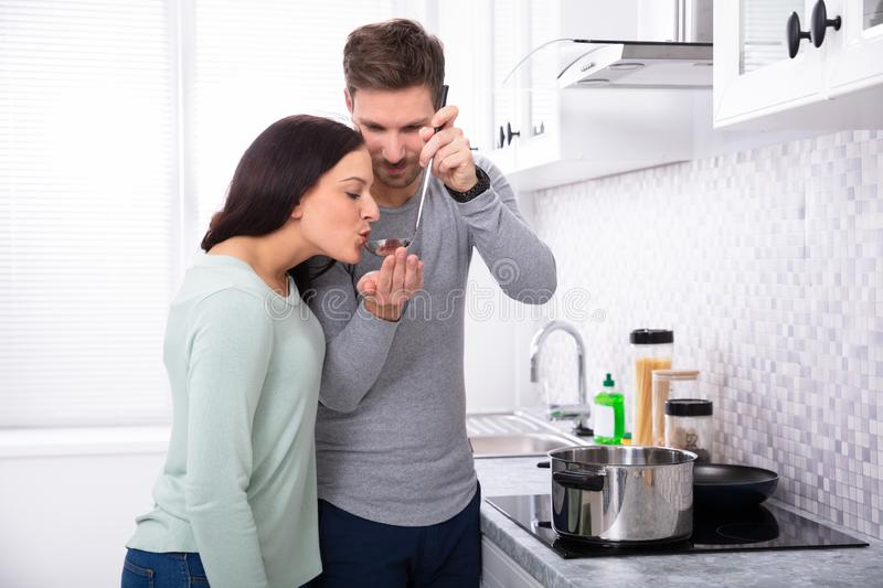 Smiling Man Tasting Food To His Wife. Young Man Making His Wife To Taste The Food In Kitchen stock photos