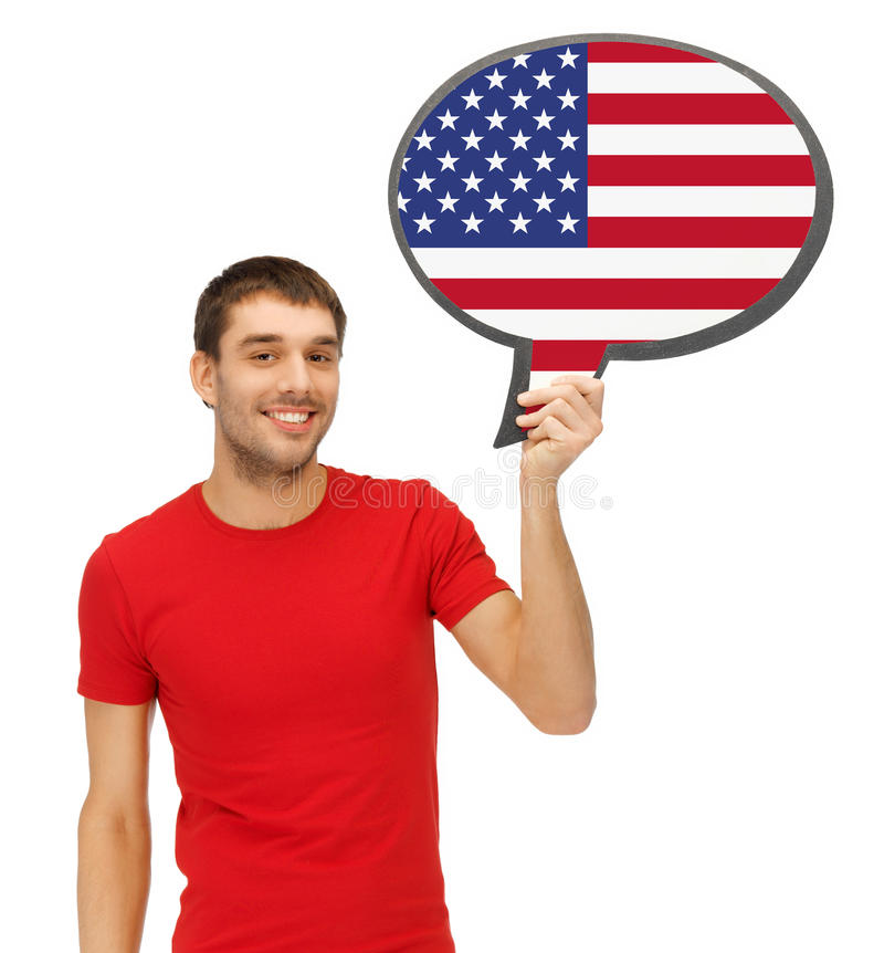 Smiling man with text bubble of american flag. Education, foreign language, english, people and communication concept - smiling young man holding text bubble of royalty free stock image