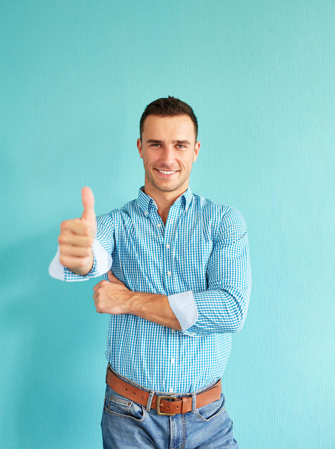 Smiling man with thumb up. Happy man with thumb up on a turquoise background stock image