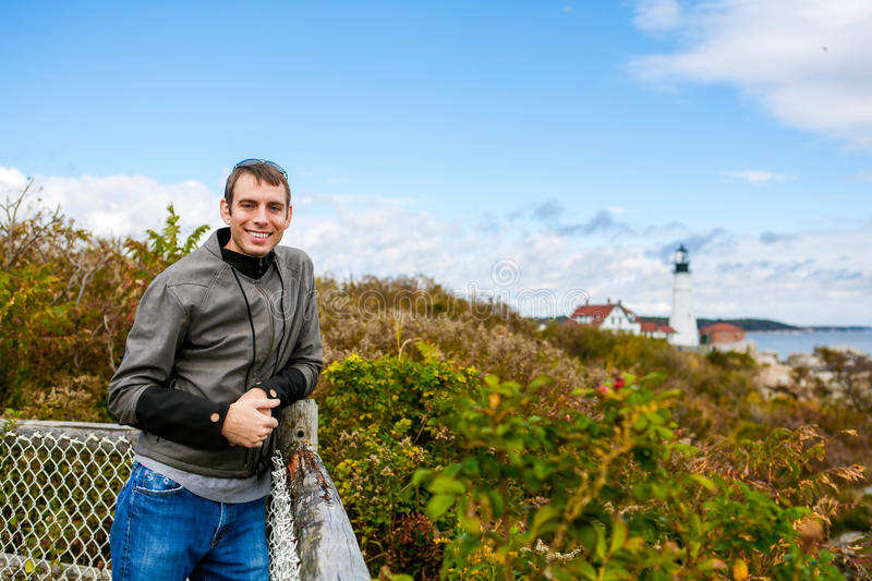 Smiling man tourist. At the background the Portland Headlight Lighthouse. In South Portland Maine stock image