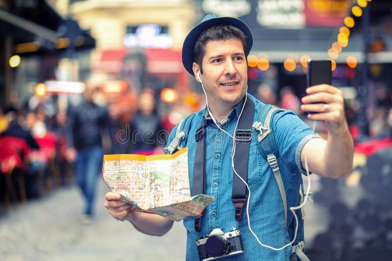 Smiling man tourist in London taking a selfie on crowded streets full of pubs, Happy middle aged male holding city map vlogging. And sharing content live on royalty free stock images