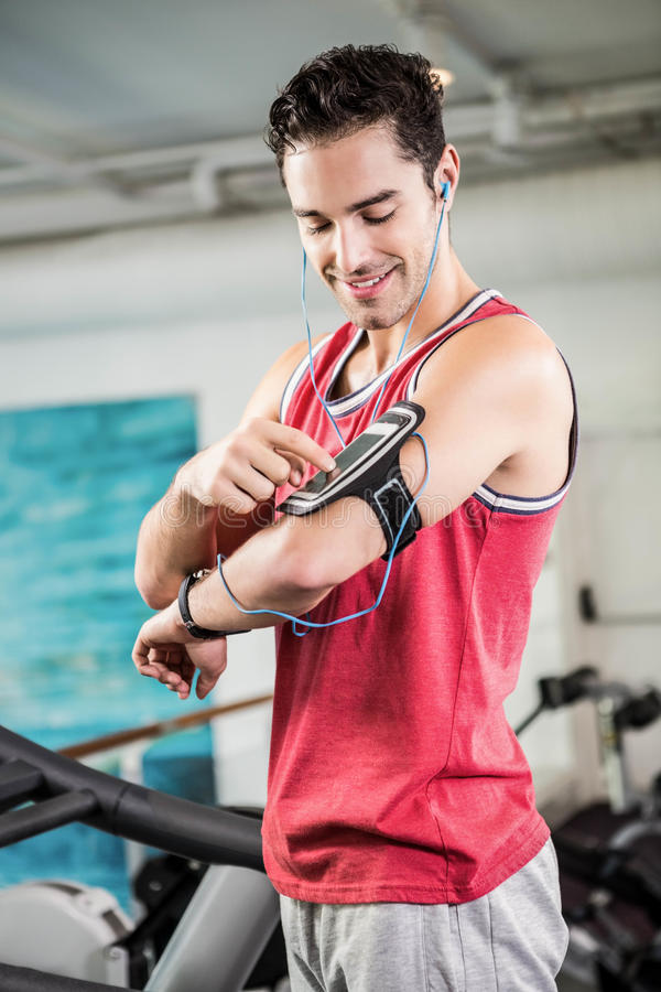 Smiling man on treadmill using smartphone stock images