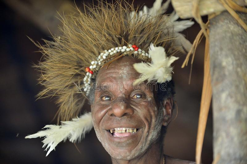 Smiling man from the tribe of Asmat people in the ritual face painting stock image