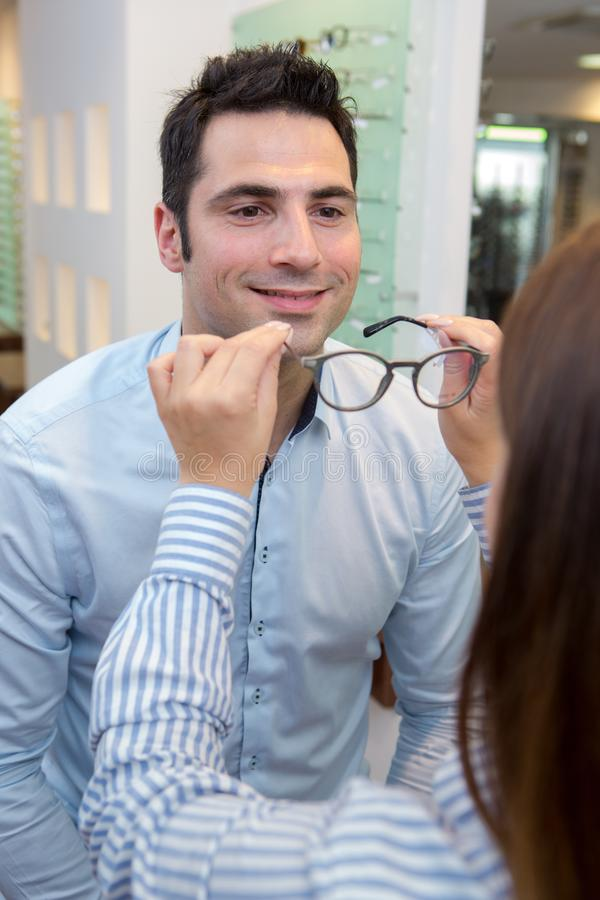 Smiling man trying on glasses in optical store royalty free stock photography