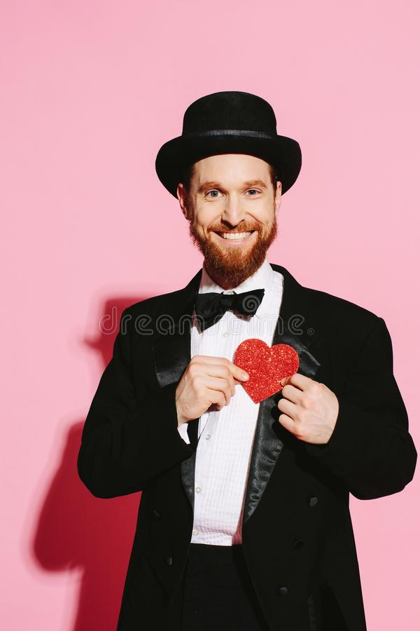 Super happy man declaring love. Smiling man in a tuxedo and top hat holding a red heart. Super happy loving man. Declaration of eternal love royalty free stock image