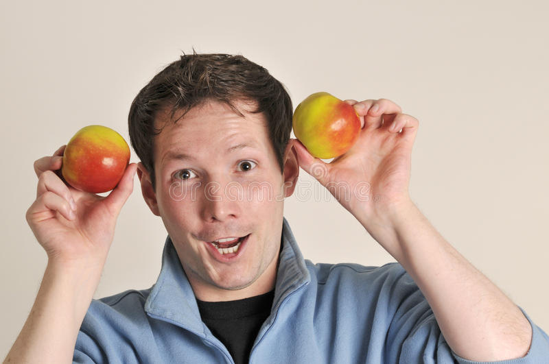 Smiling man with two apples royalty free stock photography