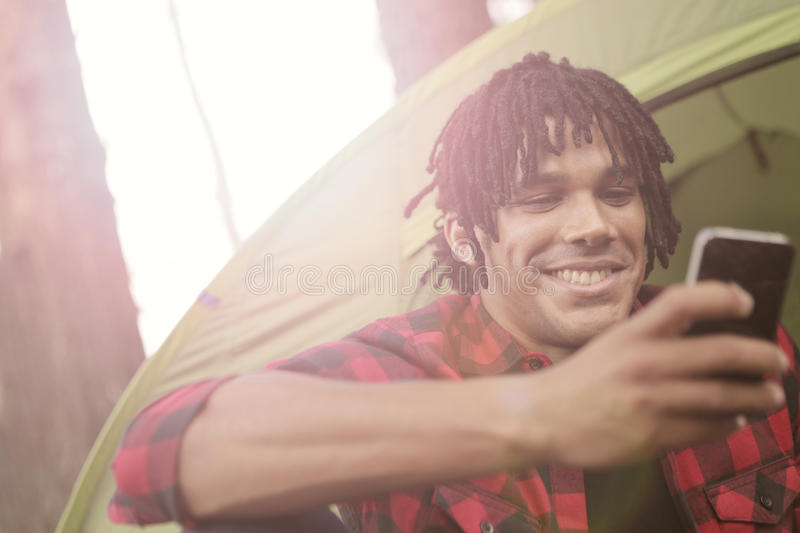 Smiling man using his phone. Man with dreadlocks smiling at his phone stock image