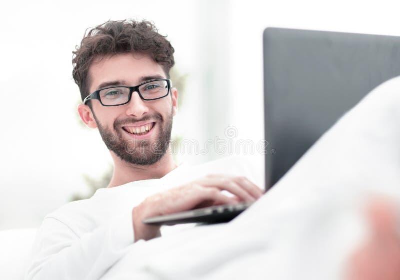 Smiling man using laptop lying on bed. Closeup.smiling man using laptop lying on bed royalty free stock photo