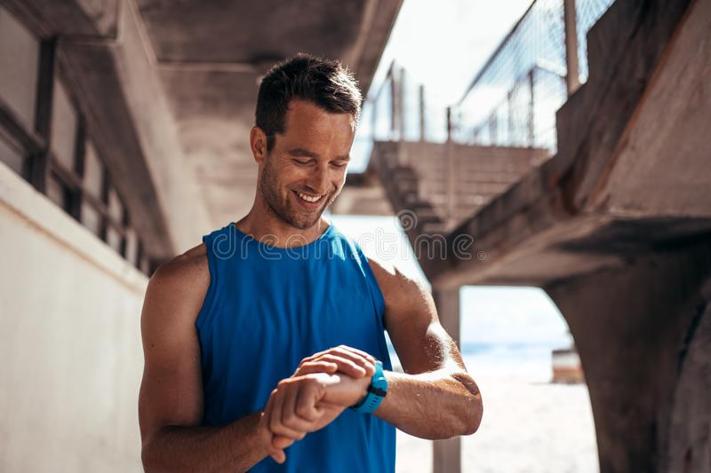 Athlete checking his progress on smartwatch fitness app stock photos