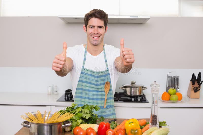 Smiling man with vegetables gesturing thumbs up in kitchen stock photo