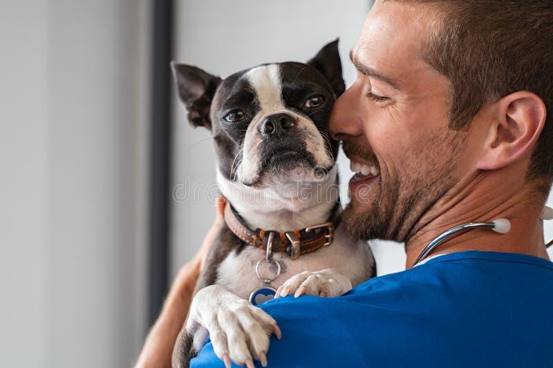 Vet cuddling pet dog stock images