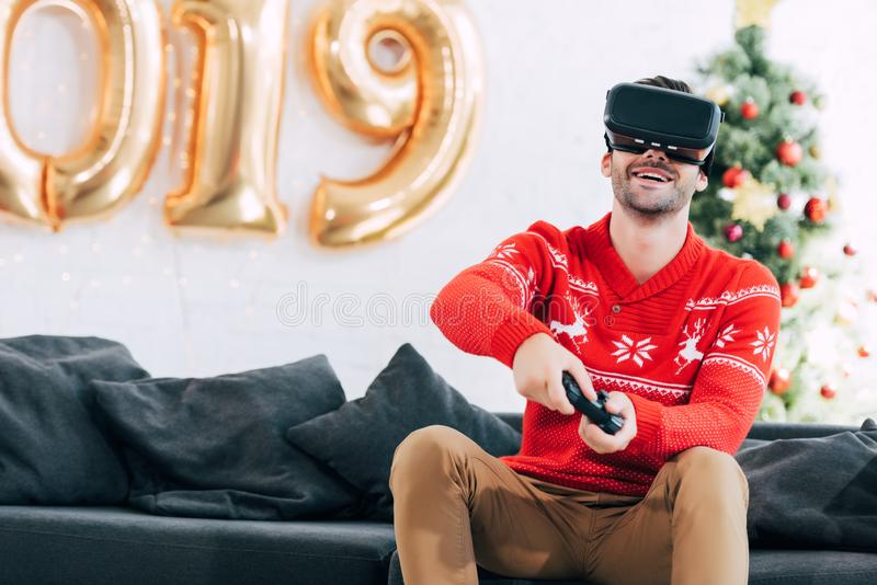 Smiling man with vr headset and joystick playing video game during 2019. New year royalty free stock photo