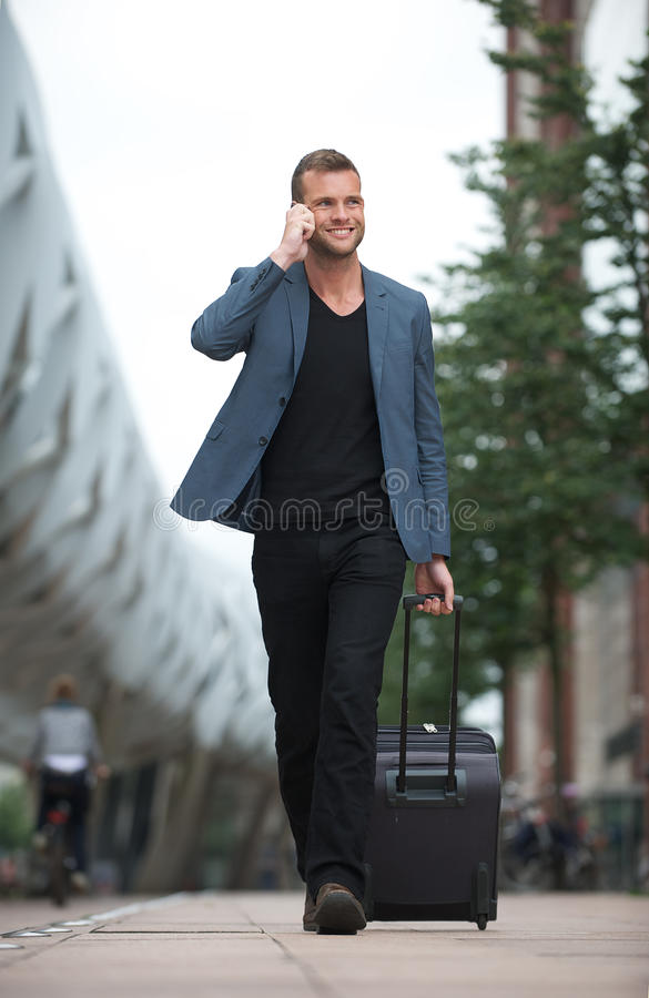 Download Smiling Man Walking In City With Cell And Suitcase Stock Photo - Image: 26374258