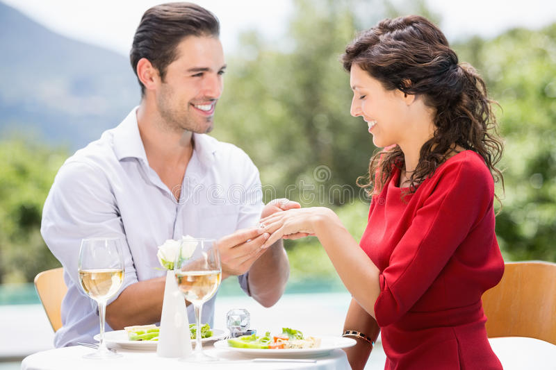 Smiling man wearing engagement ring to woman. Smiling men wearing engagement ring to women while sitting at poolside royalty free stock images