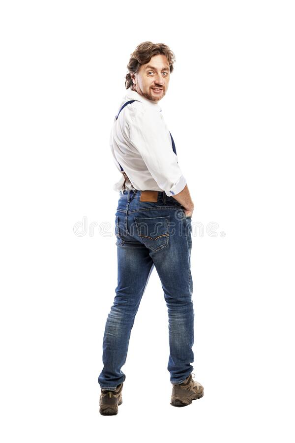 A smiling man in a white shirt and jeans turned to the camera. Back view. Full height. Isolated on a white background. stock image