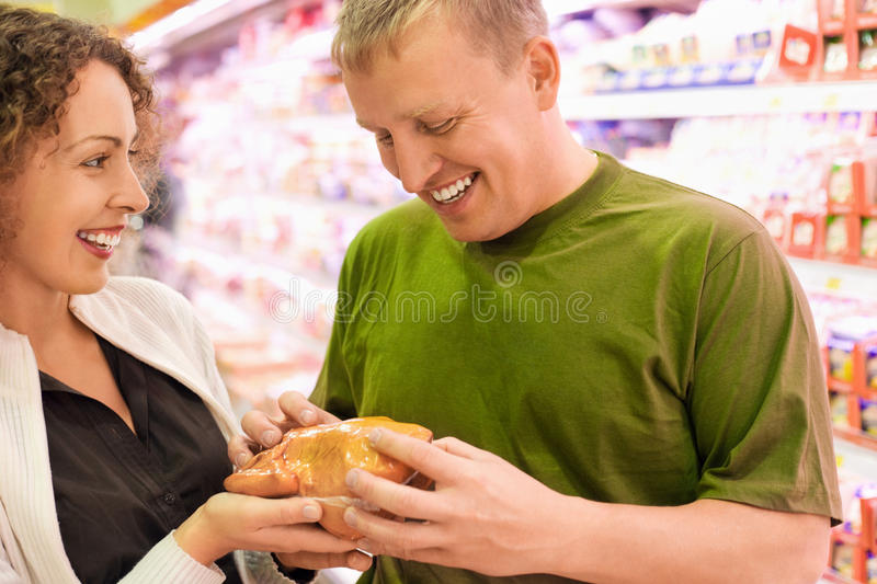 Smiling man and woman buy chicken in supermarket royalty free stock photo