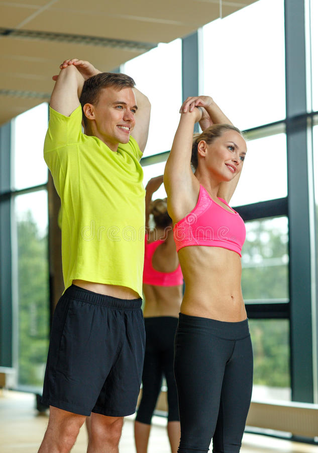 Smiling man and woman exercising in gym royalty free stock photos