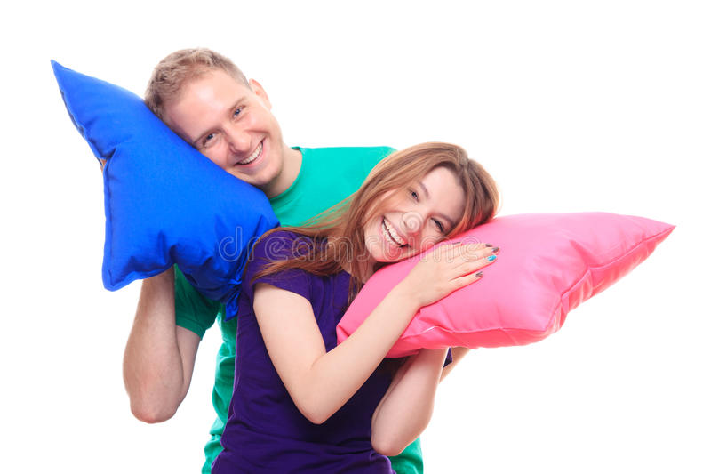 Smiling man and woman holding colorful pillows royalty free stock photos