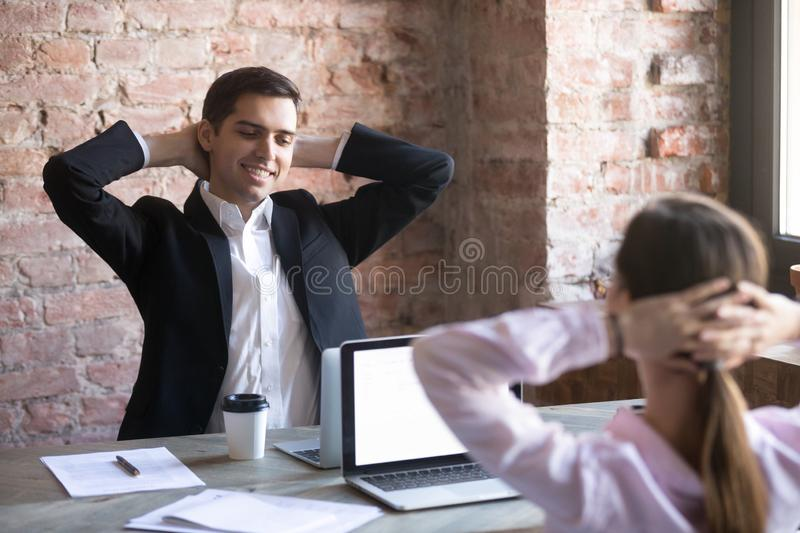 Smiling man and woman holding hands behind head. Relaxed smiling men and women holding hands behind head smiling in office at workplace. Concept of successful stock images