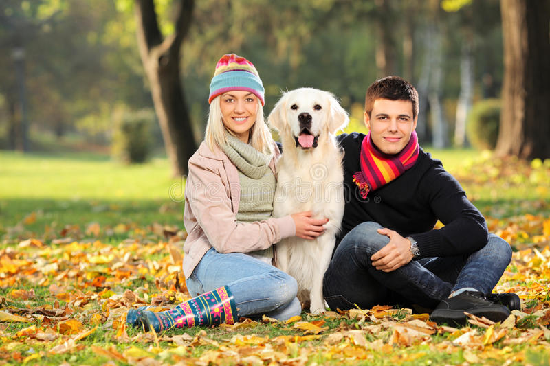 Smiling man and woman hugging a dog