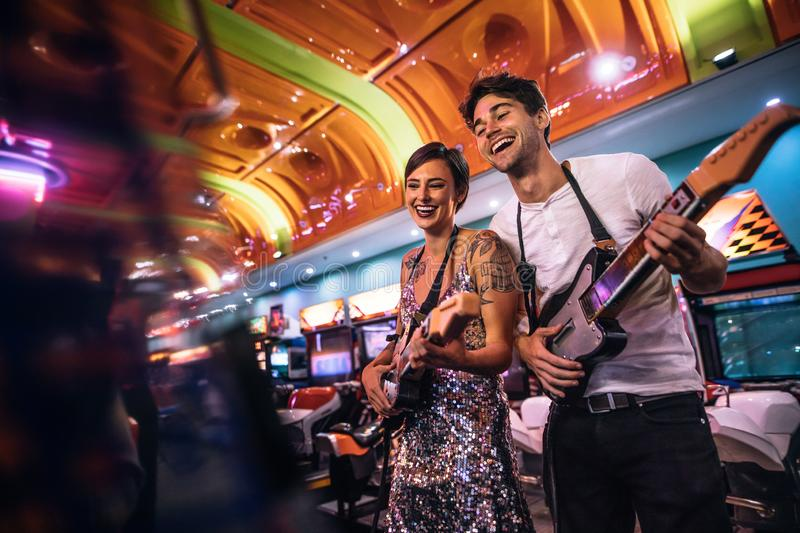 Smiling man and woman playing the guitar game at a gaming arcade stock images