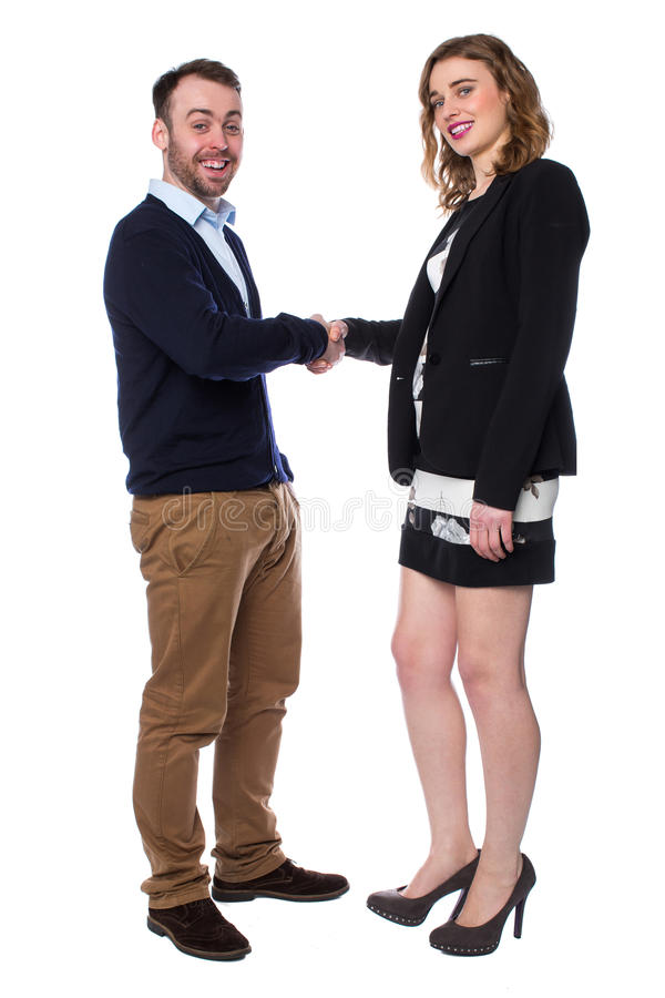 Smiling man and woman shaking hands on a deal. Smiling young men and women standing shaking hands on a deal as they agree a transaction or partnership, in royalty free stock photo