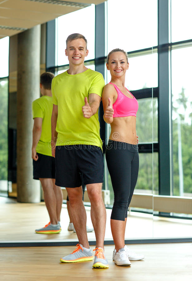 Smiling man and woman showing thumbs up in gym. Sport, fitness, lifestyle and people concept - smiling men and women showing thumbs up in gym royalty free stock image