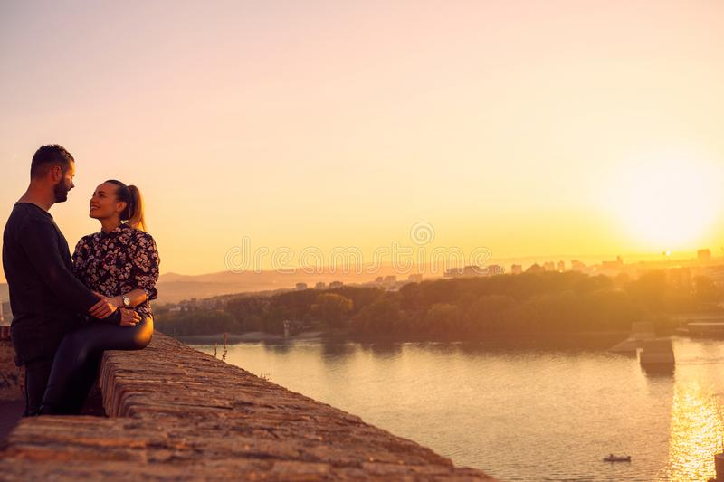 Smiling man and woman spend time together at sunset stock image