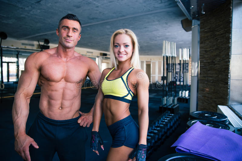 Smiling man and woman standing in gym stock photos