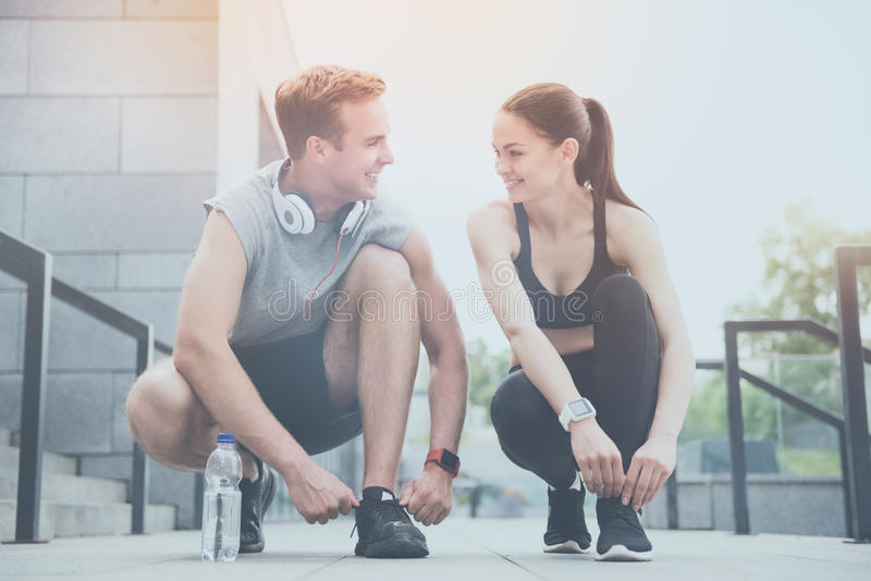 Smiling man and woman tying shoelaces together royalty free stock image