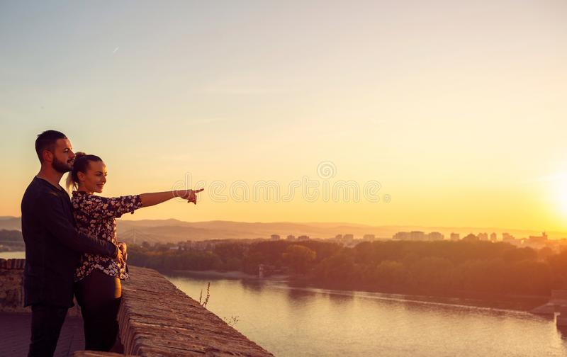 Smiling man and woman watching the sunset stock photos