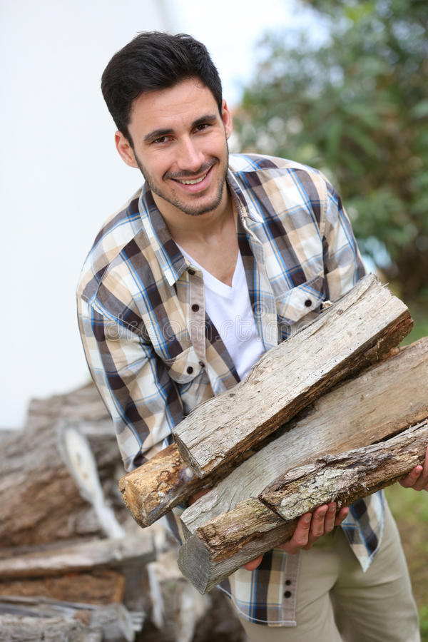 Smiling man with wood logs. Smiling man in home garden holding wood logs royalty free stock image