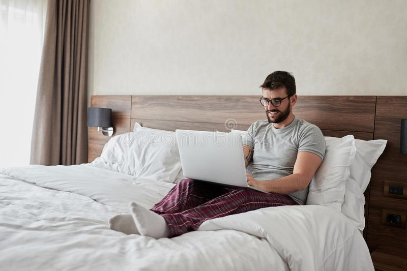 Smiling man is working with laptop, lying on bed stock images