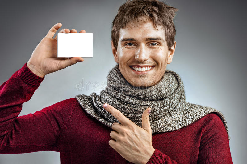 Smiling man wrapped in scarf, holding box for medicine. Photo of unhealthy man pointing finger at white packaging for medicine. Healthcare concept stock image