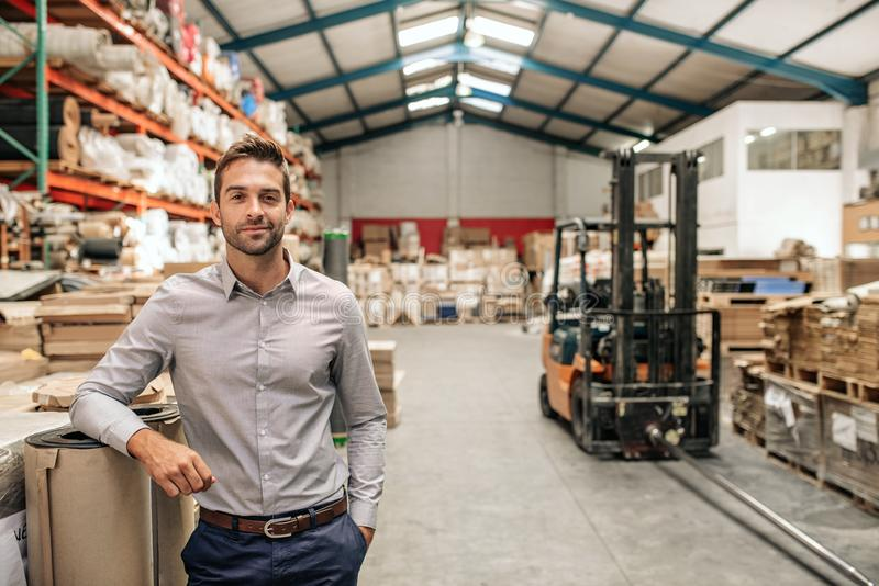 Smiling manager leaning against stock in a large warehouse stock images