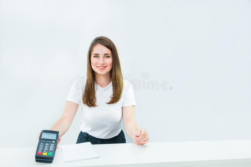 Smiling manager or seller holding payment terminal at reception desk. Contactless payment with nfc technology at shop, clinic, hot royalty free stock photos