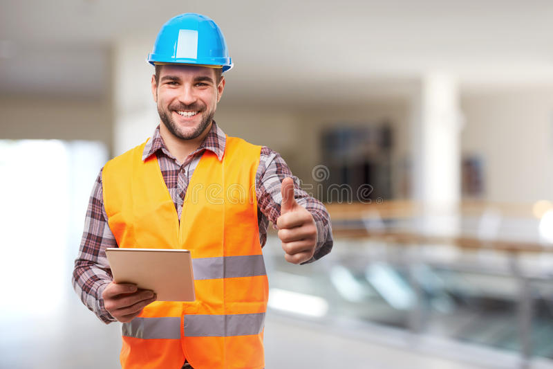 Smiling manual worker in blue helmet gesture thumb up royalty free stock photo