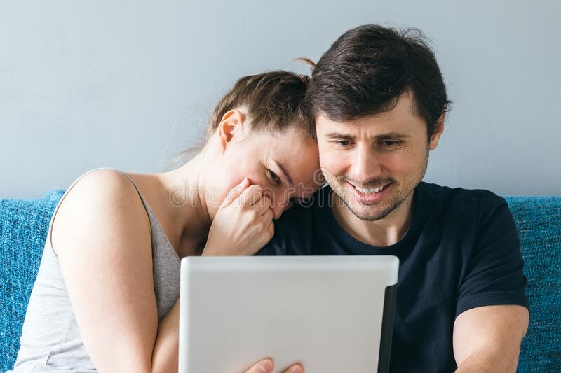 A smiling married couple have fun talking to parents or friends on an online call via tablet. A man and a woman, a family of two. Make a video call or watching stock photo