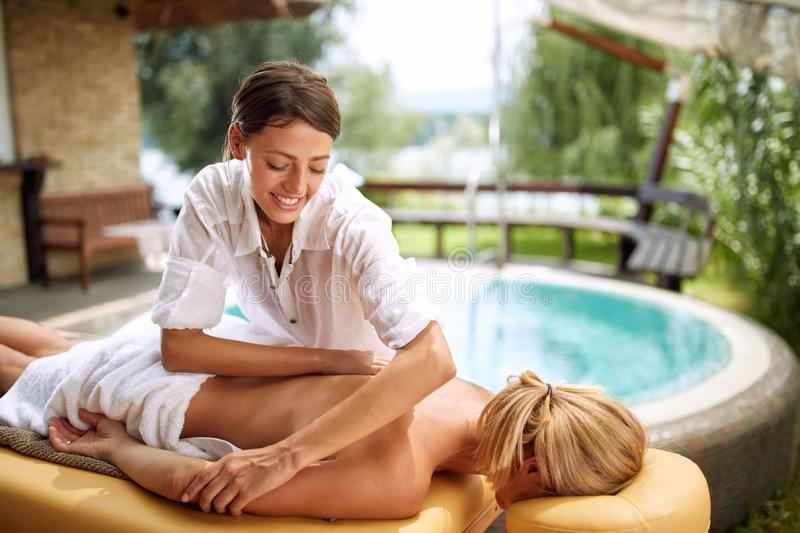 Massage therapist doing a back massage on outdoor. Smiling massage therapist doing a back massage on outdoor royalty free stock photos