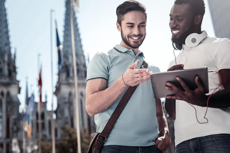 Smiling mates sharing video on tablet computer outdoors stock photo